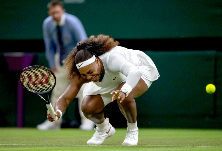 Image: Serena Williams reacts as she pulls-up injured before withdrawing from her women's singles first round match against Belarus's Aliaksandra Sasnovich on the second day of the 2021 Wimbledon Championships in London on June 29, 2021.