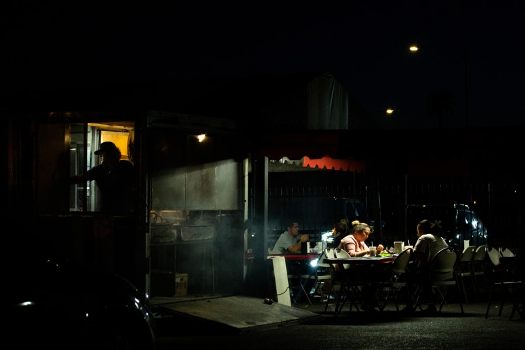 Image: Customers eat in the outdoor dining area of a restaurant in Phoenix on April 22, 2021.