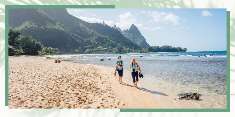 """Woman with son walking on beach. Malama Hawaii is a statewide volunteer program that helps travelers experience Hawaii beyond its natural beauty. Malama means to \""""give back\"""" or \""""take care.\"""""""