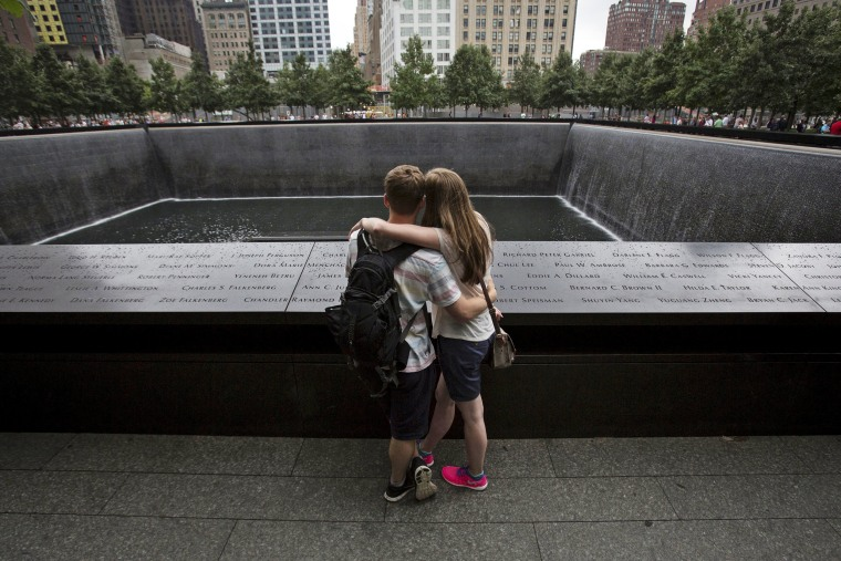 Image: People embrace at the National September 11 Memorial and Museum in Lower Manhattan in New York