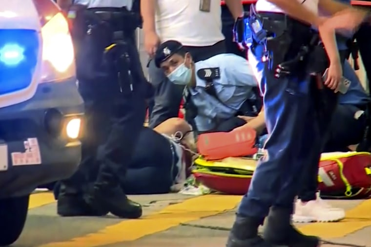 A police officer receives medical treatment after being stabbed in Hong Kong on Thursday.