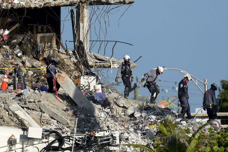 Image: Search and rescue workers descend from the rubble pile at the Champlain Towers South condo building, where scores of people remain missing one week after it partially collapsed on July 2, 2021, in Surfside, Fla.