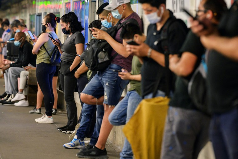 Image: Commuters looks at their mobile phones as they wait for the subway in New York on June 10, 2021.