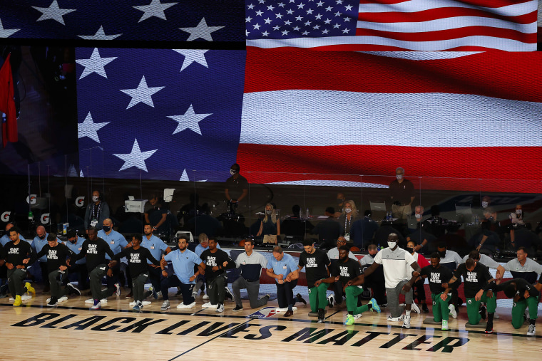 Image: The Boston Celtics and the Memphis Grizzlies take a knee during the National Anthem prior to the start of their game on Aug. 11, 2020 in Lake Buena Vista, Fla.