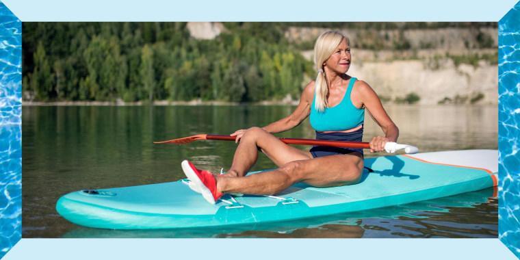 Senior woman paddleboarding on lake in summer