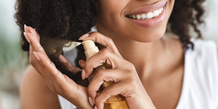 Woman Applying Essential Oil Spray On Her Curly Brown Hair At Home