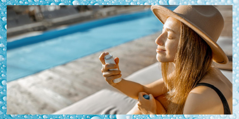 Young woman spraying water on her face while relaxing on the sunbed near the swimming pool