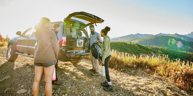Father and daughters preparing to begin backpacking trip at back of car