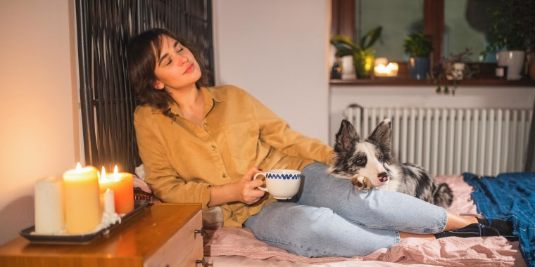 Woman with purebred dog relaxing on bed at home
