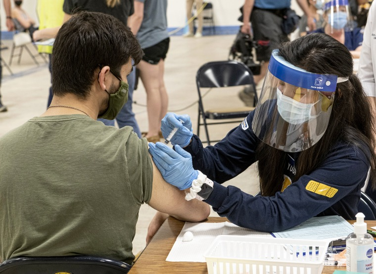 Image: A Kent State University student gets his Johnson Johnson Covid-19 vaccination from a Kent State nursing student in Kent, Ohio.