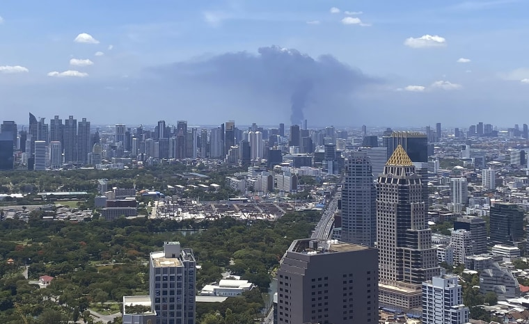 Image: In a view from downtown Bangkok, giant plumes of smoke can be seen rising from the Samut Prakan province area in central Thailand,