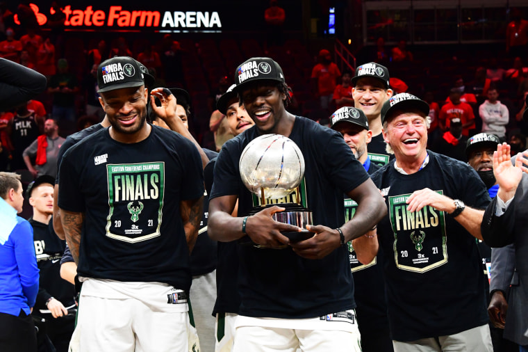 P.J. Tucker #17 of the Milwaukee Bucks and Jrue Holiday #21 celebrate with the Eastern Conference Finals Trophy after game 6 of the Eastern Conference Finals of the 2021 NBA Playoffs on July 3, 2021, in Atlanta.