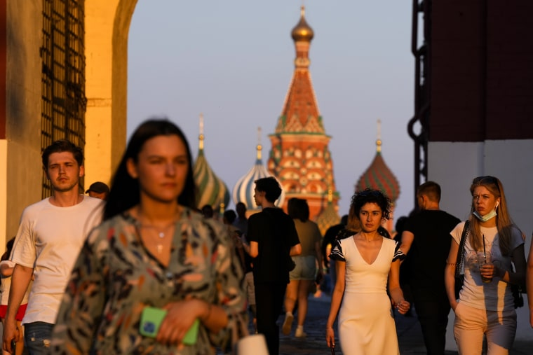 Image: People walk at Red Square during sunset in Moscow on June 24, 2021.