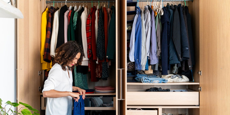 Woman standing next to her closet, holding jeans, clearing out her wardrobe. Here are the best hangers for clothes in 2021. Shop plastic hangers, velvet hangers, and wooden hangers from Amazon, The Container Store and more.