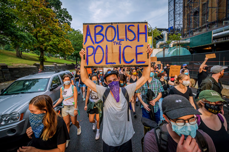 Image A participant holding a Abolish Police sign at a protest.