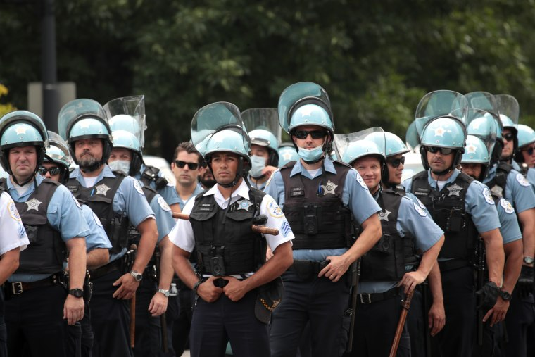Police officers stands guard as demonstrators stage a rally and march to protest police brutality on August 15, 2020 in Chicago.