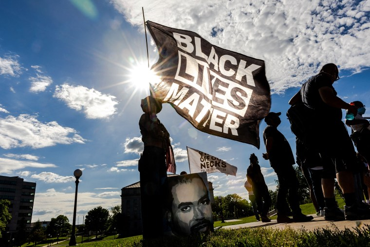 A woman holds a Black Lives Matter flag during an event in remembrance of George Floyd outside the Minnesota State Capitol on May 24, 2021 in Saint Paul, Minn.