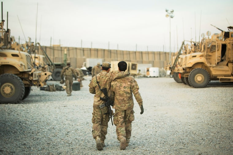 Image: A U.S. soldier from the 3rd Cavalry Regiment walks with the unit's Afghan interpreter before a mission near forward operating base Gamberi in the Laghman province of Afghanistan