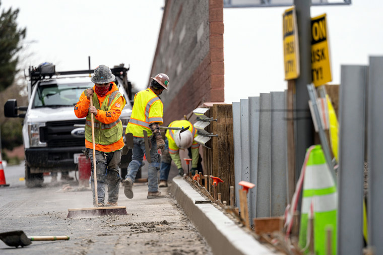 Contractors work on a road under repair along Highway 101 in San Mateo, Calif, on March 17, 2021.