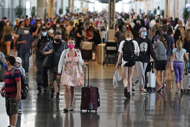 Image: Travelers walk through Salt Lake City International Airport in Salt Lake City on July 1, 2021.
