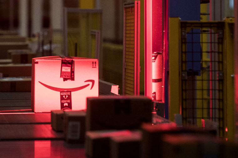 Image: Packages are scanned while moving along a conveyor belt at the Amazon fulfillment center in Robbinsville, N.J.