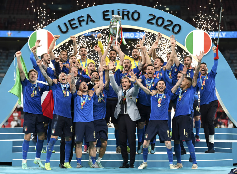 Image: Italy's team celebrates with the trophy on the podium after winning the Euro 2020 soccer championship final between England and Italy at Wembley stadium in London on July 11, 2021.