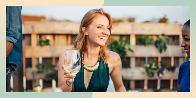 Smiling young woman talking with friends while sitting at rooftop
