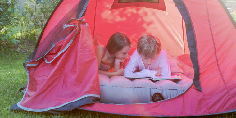 Boy and girl reading lying in a red tent with a book