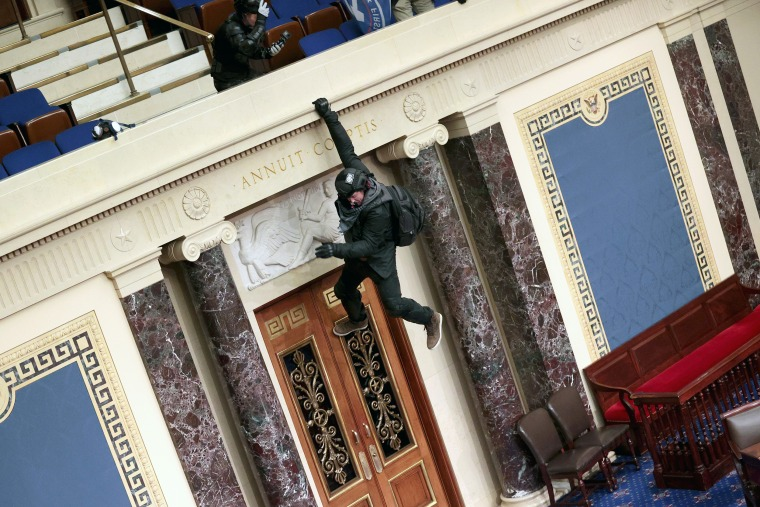 A rioter hangs from the balcony in the Senate Chamber on Jan. 6, 2021.
