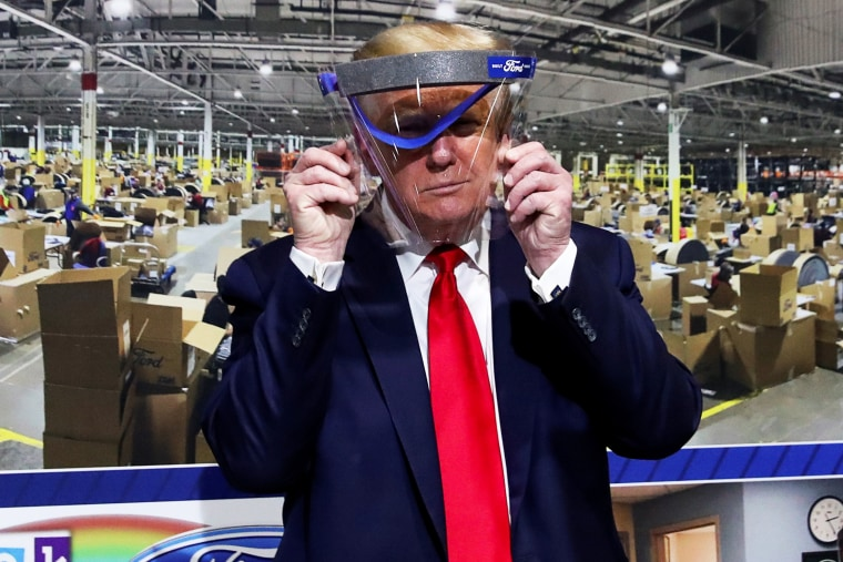 President Donald Trump holds up a protective face shield that was handed to him during a tour at the Ford Rawsonville Components Plant in Ypsilanti, Mich., on May 21, 2020.