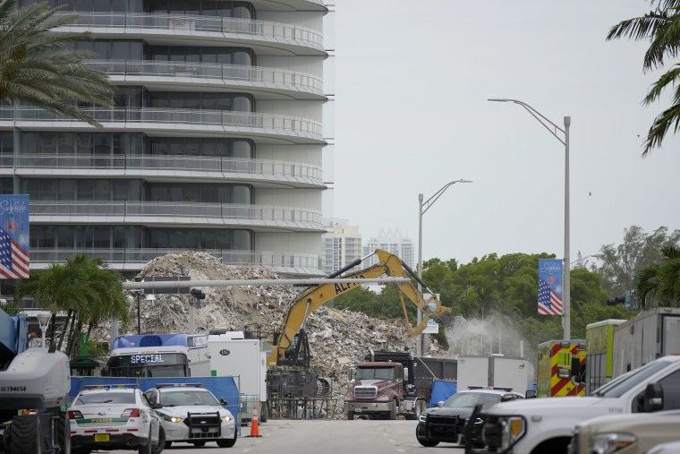 Image: An excavator removes the rubble of the demolished section of the Champlain Towers South building, as recovery work continues at the site of the partially collapsed condo building