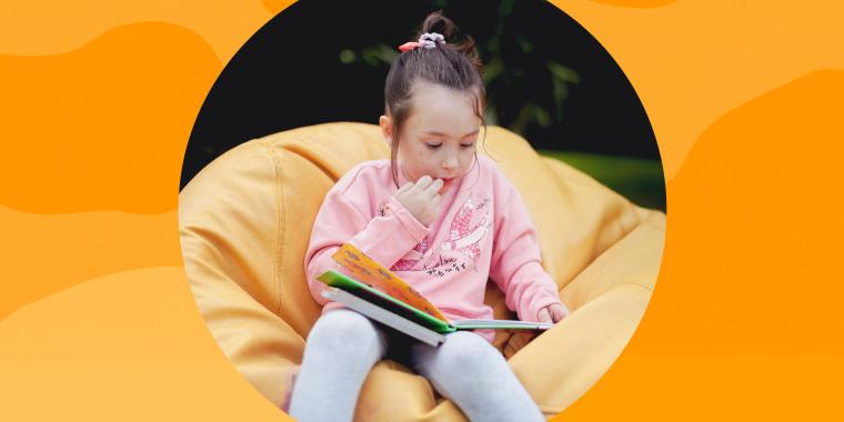 Little girl on beanbag chair reading a book