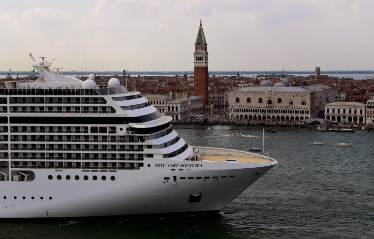Image: Tugboats escort the MSC Orchestra cruise ship across the basin past the Bell Tower and the Doge's palace as it leaves Venice