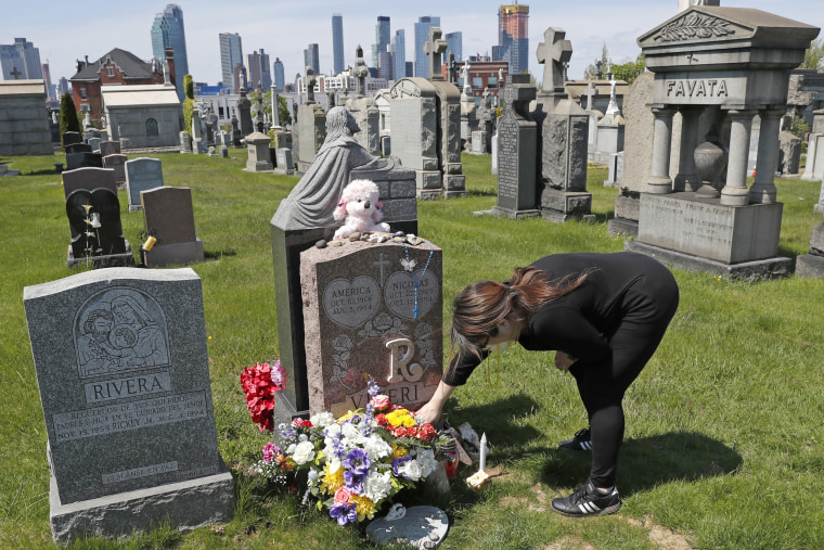 Sharon Rivera adjusts items left at the grave of her daughter, Victoria, at Calvary Cemetery, N.Y., on May 10, 2020.