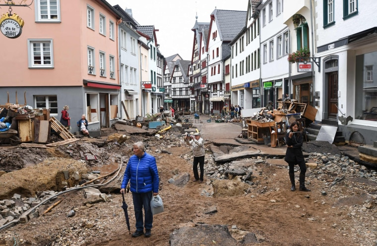 People walk through the debris in the pedestrian zone in Bad Muenstereifel, western Germany, on July 16, 2021.