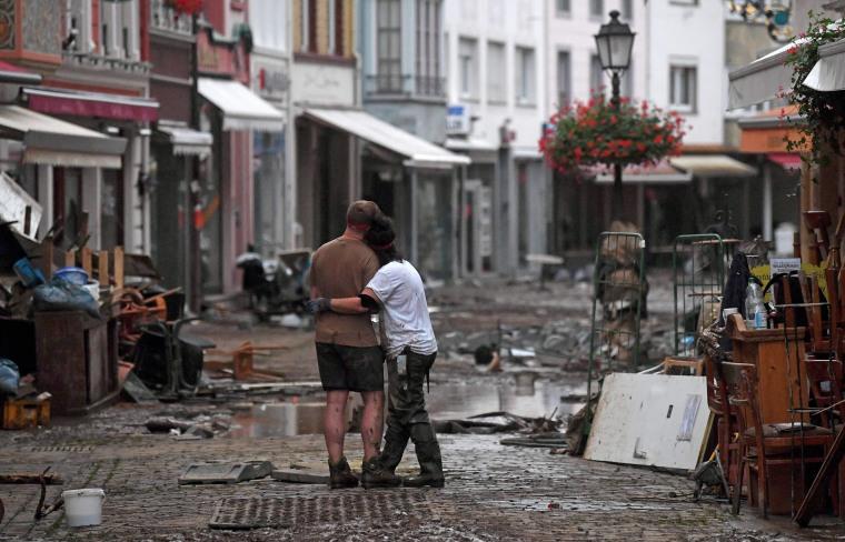 A couple hug as they stand amid debris in Bad Neuenahr-Ahrweiler on July 15, 2021.