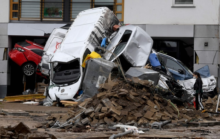 A woman looks at cars and rubble piled up in a street in Bad Neuenahr-Ahrweiler, western Germany, on July 16, 2021.