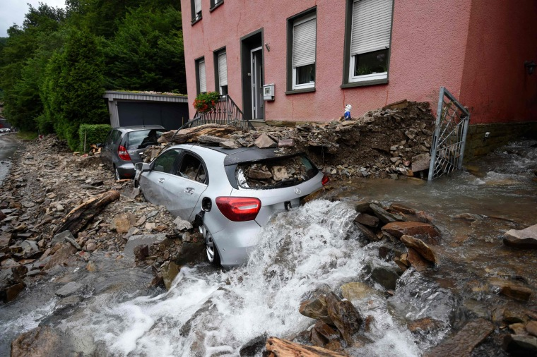 Water runs past a house with a car covered in rubble after heavy rain and floods caused major damage in Hagen, western Germany, on July 15, 2021.