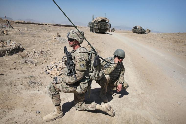 An Afghan interpreter monitors radio traffic during a patrol with U.S. soldiers near Kandahar, Afghanistan, in 2014.