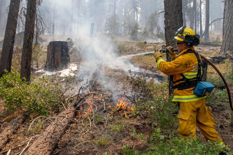 A firefighter out of California puts out hot spots on the Bootleg Fire north of Bly, Ore., on July 17, 2021.