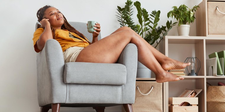 Young woman in headphones lying on armchair listening to music and drinking coffee
