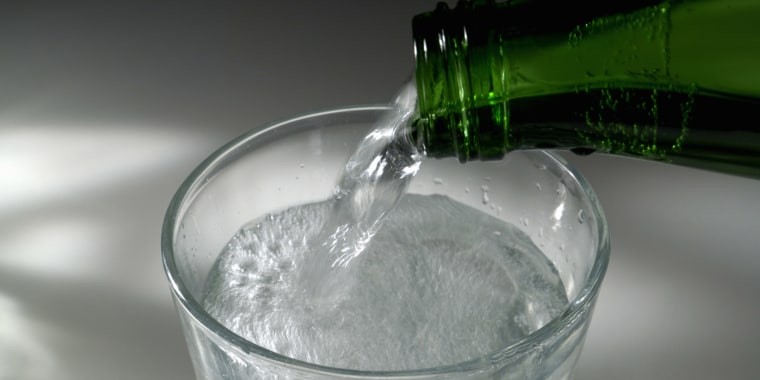 Carbonated water being poured into glass, elevated view