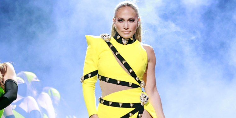 Jennifer Lopez in a one-shoulder bright yellow dress in front of smoke on stage at the Global Citizen VAX LIVE: The Concert To Reunite The World.