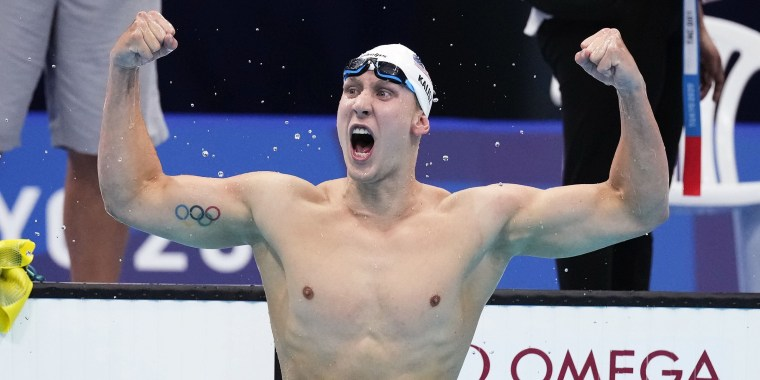 Chase Kalisz pumps his fists triumphantly in the air while standing in a pool after finishing his swim