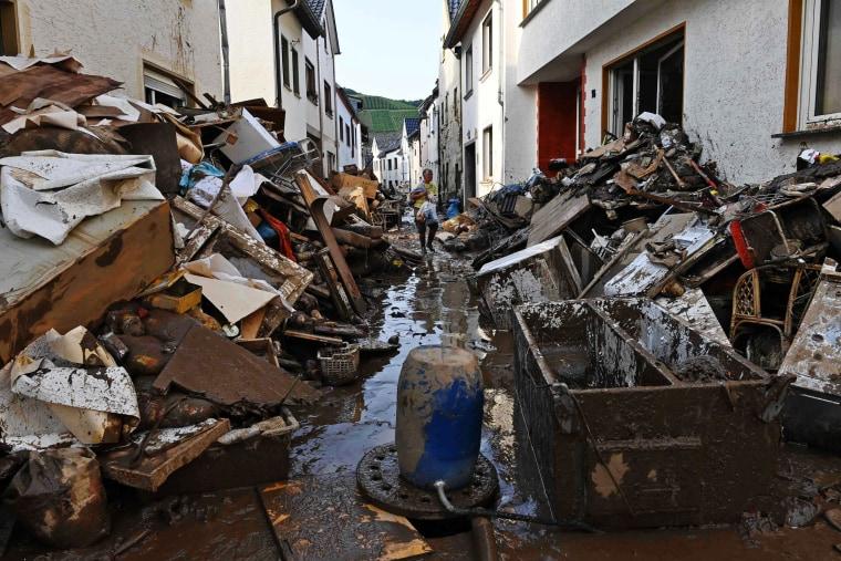 A resident walks in a street full of debris and mud in the city of Dernau, western Germany, on July 18, 2021.