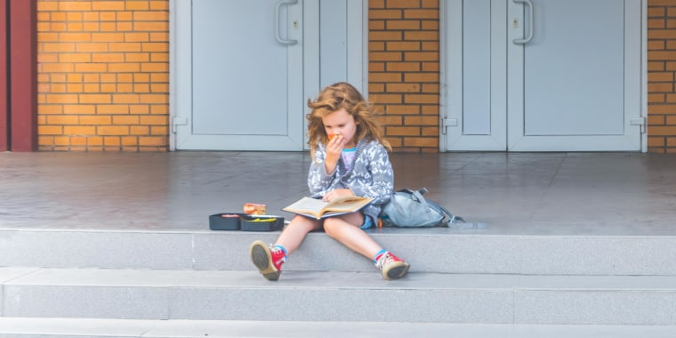 Sunny day at school, kindergarten girl, eating from her lunchboxes and reading a book