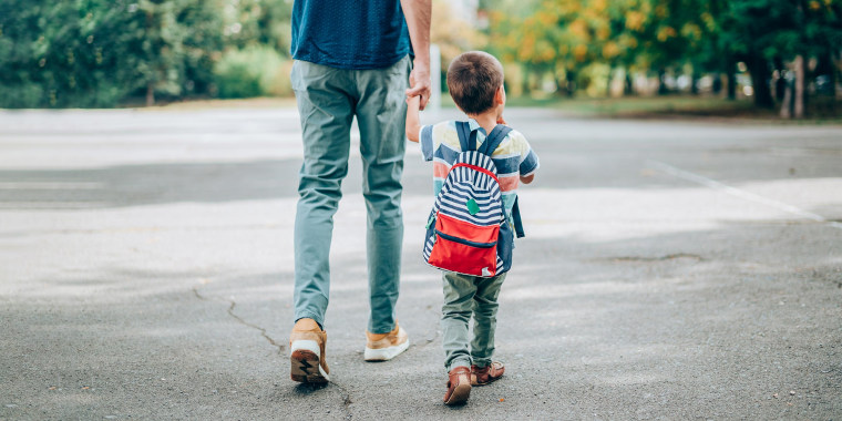 Father and son with backpack walking in schoolyard