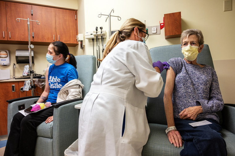 Image:  A cancer patient receives a Covid-19 vaccine in an oncology unit at the James Graham Brown Cancer Center on April 2, 2021 in Louisville, Ky.