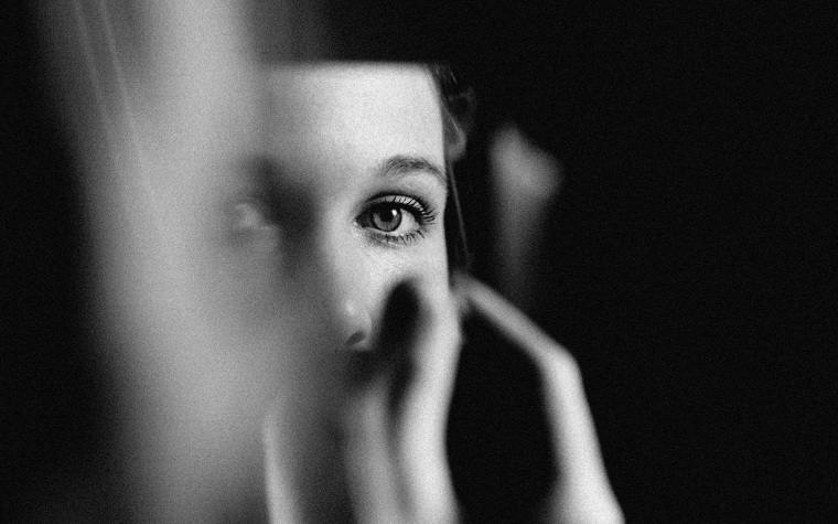 Image of a woman's eyes in a sliver of mirror.