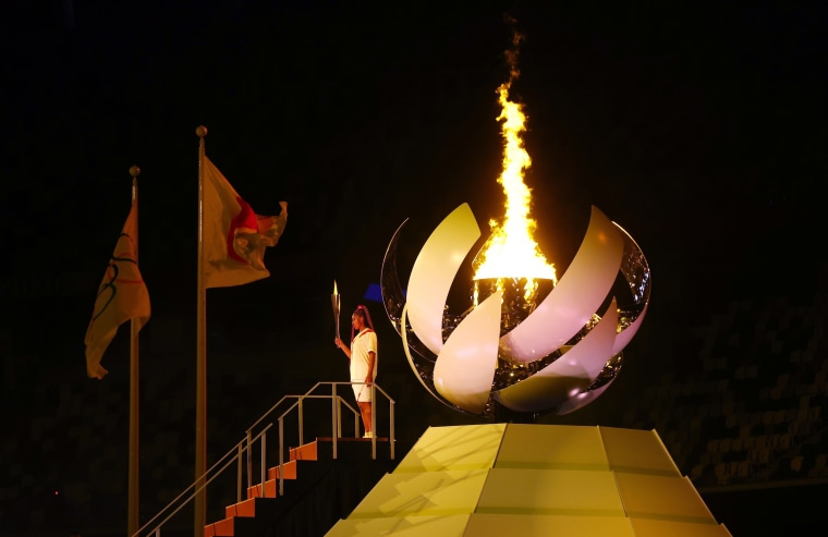 Naomi Osaka of Japan holds the Olympic torch after lighting the Olympic cauldron.